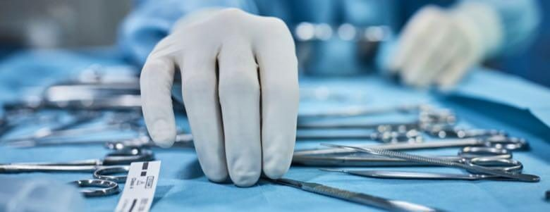 doctor picking up medical tools