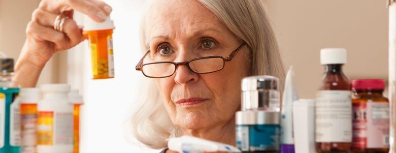elderly lady looking at prescription bottles