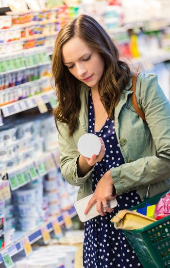 young woman shopping in a grocery story, examining an item