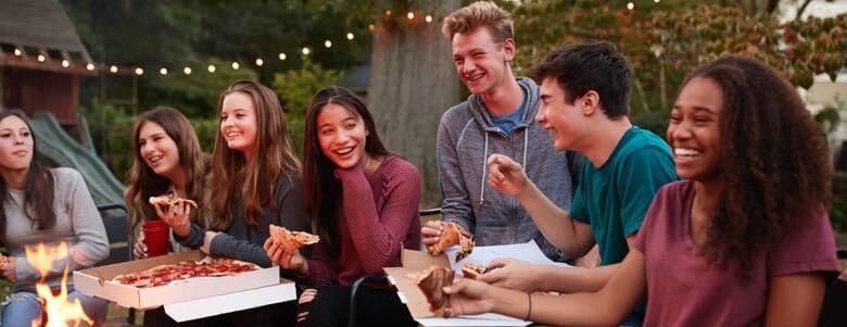 teens outside eating pizza