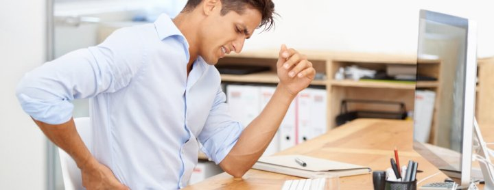 Man with back pain sitting at his desk