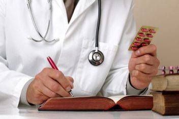 Doctor holding up pills and writing in a book