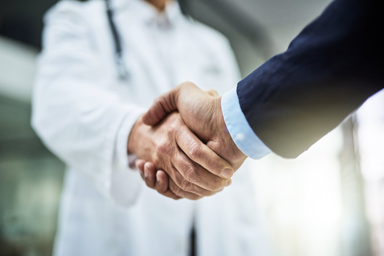 doctor shaking businessman's hand
