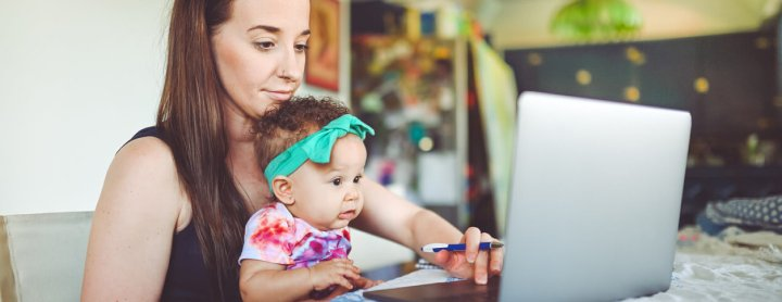 Woman holds her baby while at the computer