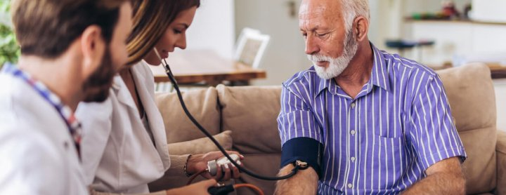 Man gets blood pressure checked by doctor