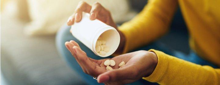 Woman pouring pills out of prescription bottle