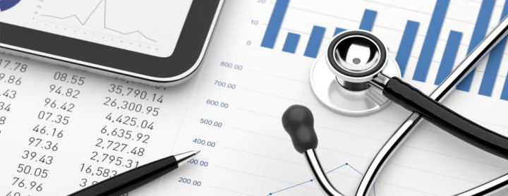 Tablet and stethoscope on table with financial statements