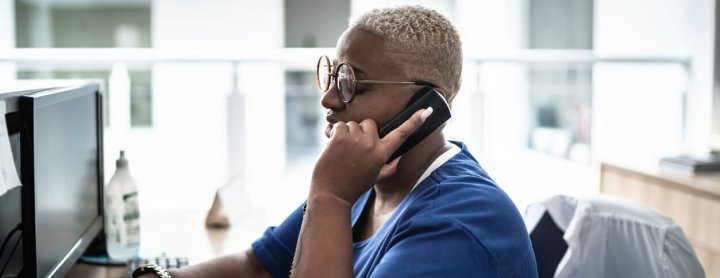 Hospital receptionist speaking to someone on the phone