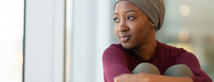 Woman in head scarf staring out window