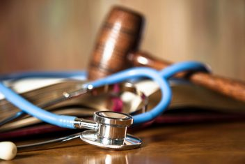 Judge's gavel and stethoscope on court room table.