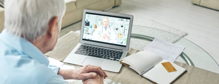Elderly man using laptop for telemedicine visit with doctor