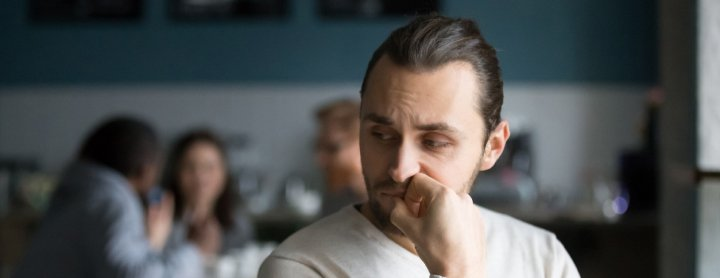 Man sitting nervously in coffee shop with other people
