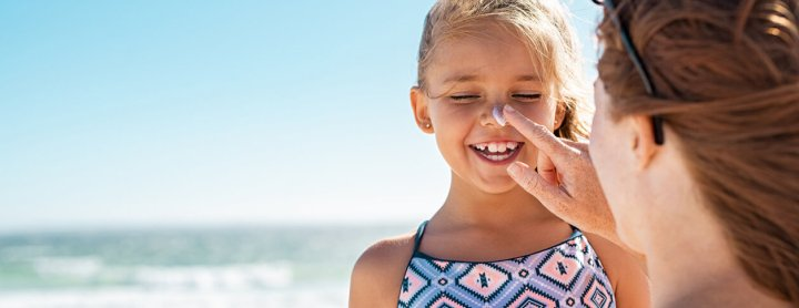 Woman putting sunscreen on child's face