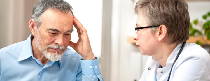 Doctor discussing chronic pain with man that has headache