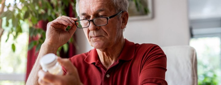 Elderly man reading his prescription pill label