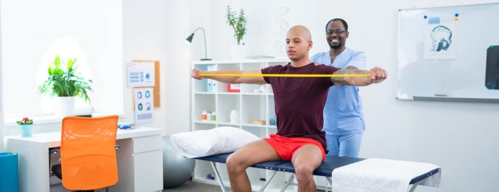 Physical therapist assisting his patient with exercises