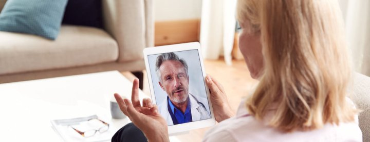Female patient explains health concerns to doctor over telemedicine visit