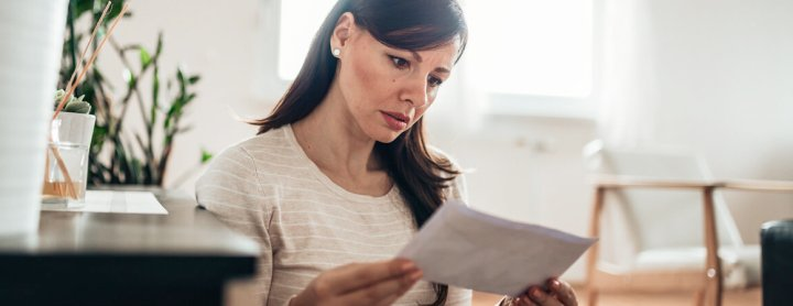Woman with a disappointed look on her face reading a letter