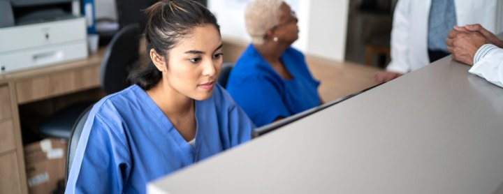 Receptionist at hospital setting at front desk