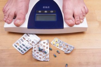 feet on scale and pills on the floor