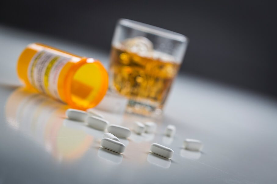 Open Pill Bottle Scattered on Table with Alcohol