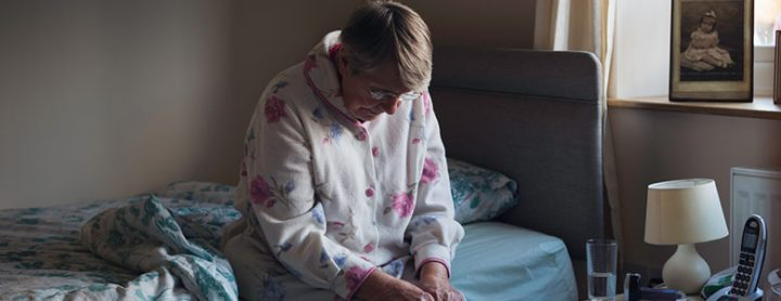 Elderly woman sitting alone on her bed