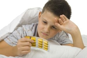 Boy holding packet of pills
