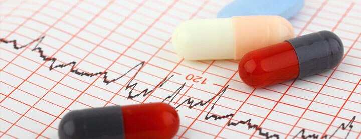 Pills laid out on paper showing heart activity readings