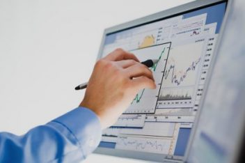 hand marking a chart on a computer screen