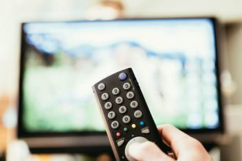 Hand pointing remote towards tv