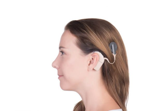 Woman with cochlear implant in ear