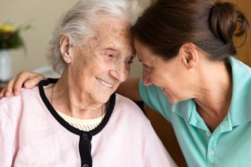 Caregiver and senior woman embracing