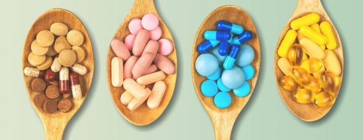 Four wooden spoons holding pills