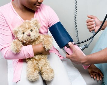 Doctor checking girl's blood pressure