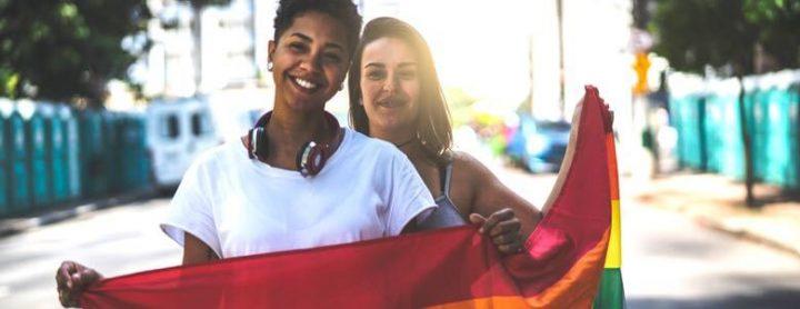lgbtq couple holding a rainbow flag