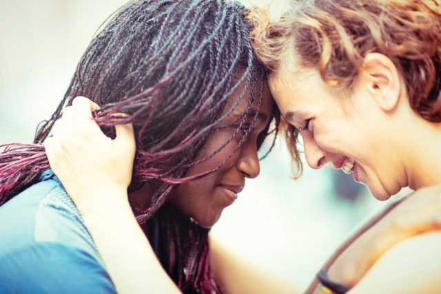 Black woman and white woman embracing each other lovingly