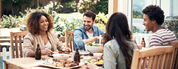 Group of friends enjoy dinner at a table outside