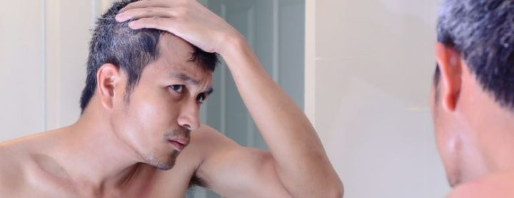 man checking gray hairs