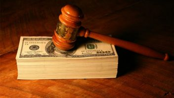 gavel resting on a stack of hundred dollar bills
