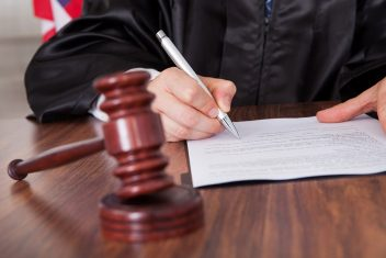 Judge signing a document with a gavel in the foreground