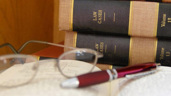 law books with one opened with glasses and a pen resting on top