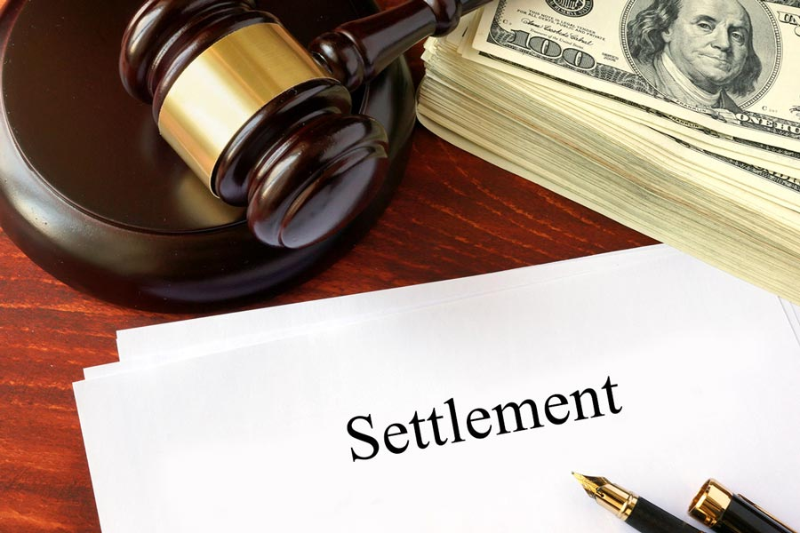 gavel with a stack of hundred dollar bills over a settlement form