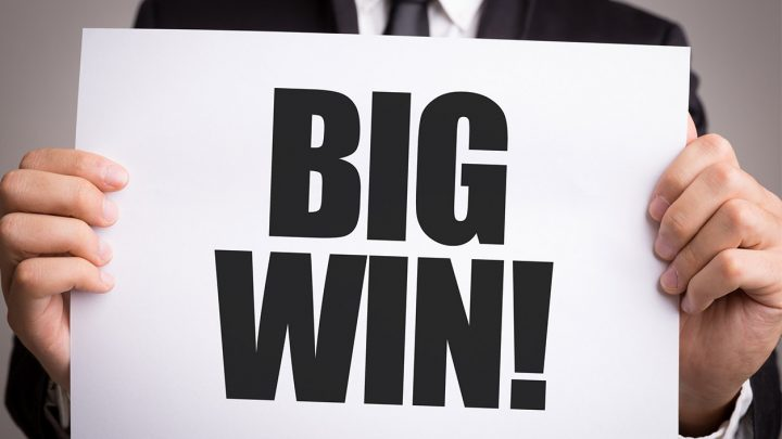 "Man in suit holding a paper that read ""Big Win!"""