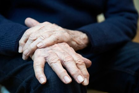 Elderly Person's Wrinkled Hands on Lap
