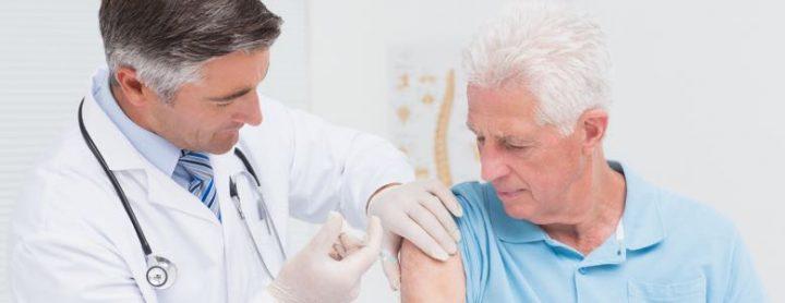 doctor giving an elderly man a shot
