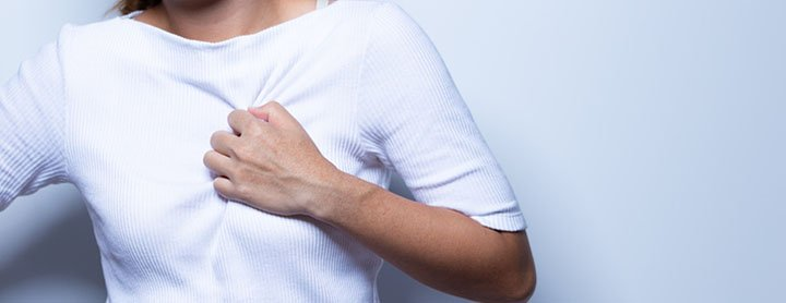 Woman clutches her chest in pain