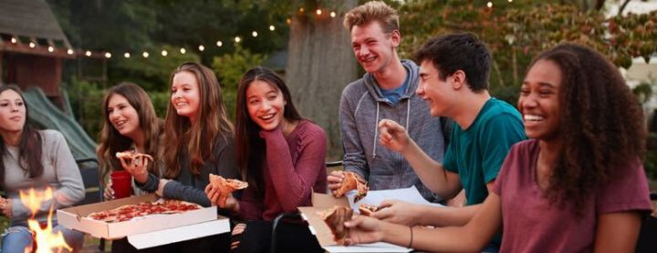 teens outside eating pizza