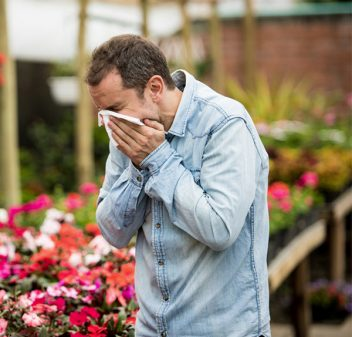 Man standing near flowers and sneezing